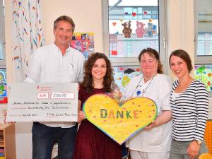 Prof. Dr. Lutz Weber (l.) und Erzieherin Petra Felten (2.v.r.) freuten sich über die Spende der Sparkasse für das Spielzimmer. Foto: Uniklinik Köln