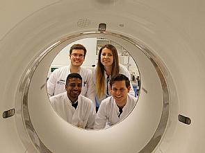 """Dr. Gérard Nisal Bischof (l.u.) mit einem Teil seiner Arbeitsgruppe """"Multimodale Bildgebung neuronaler Netzwerke"""" in der Nuklearmedizin, Foto: Uniklinik Köln"""