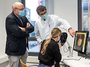Prof. Dr. Tim U. Krohne (Mitte), Leiter des Netzhaut-Schwerpunkts des Zentrums für Augenheilkunde, und Dr. Christoph Stosch (links), Leiter des KISS, demonstrieren den neuen Funduskopie-Simulator, Foto: Christian Wittke